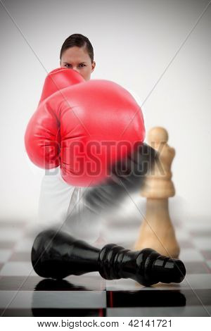 Woman in boxing gloves knocking over chess pieces on chess board