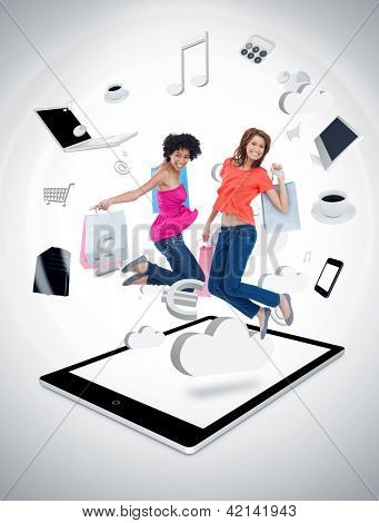 Two smiling women jumping on a tablet pc against a digital gray background