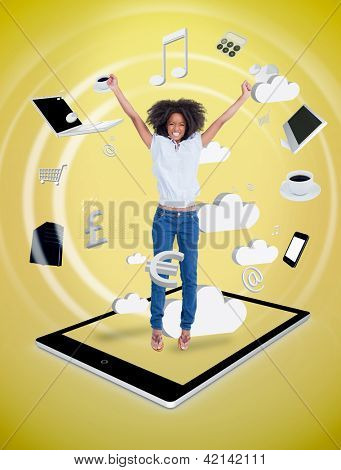 Happy woman jumping on a tablet pc against a digital yellow background