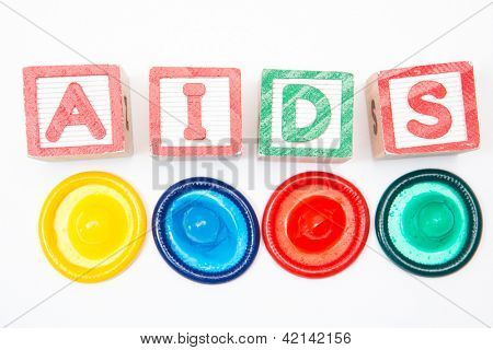 Wood blocks spelling out aids with four colourful condoms on white background