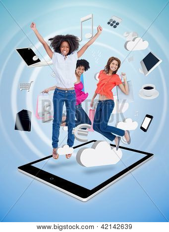 Three cute women jumping on a tablet pc against a digital blue background