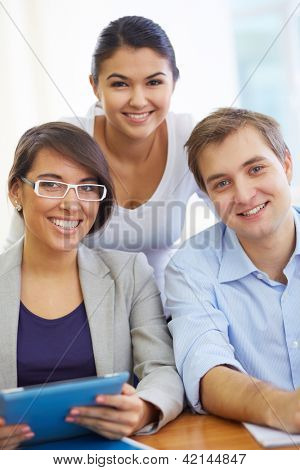 Portrait of three friendly students looking at camera