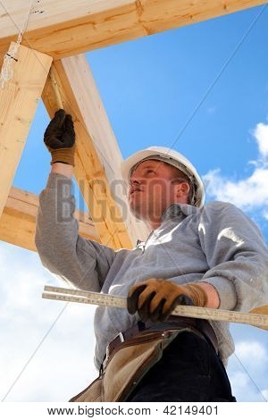 roofer at work with wooden  roof construction
