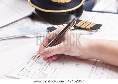 Close up of an airplane pilot hand filling in an flight plan with equipment including hat, epaulettes and other documents in background