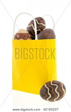 Yellow shopping bag with chocolate eggs isolated over white background