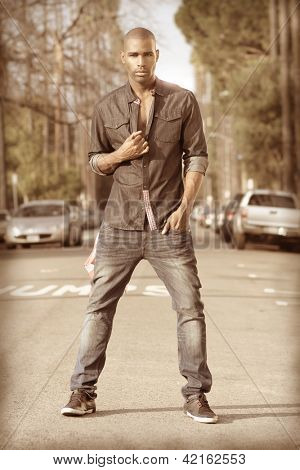 Stylized fashion portrait of a male model in urban trendy clothing in street setting with vintage retro look and feel