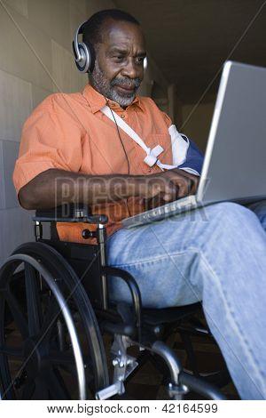 Injured senior African American man using laptop while listening music on wheelchair