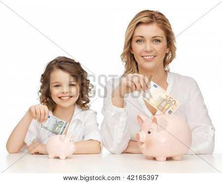 mother and daughter with piggy banks and paper money