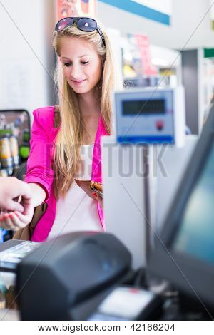 Beautiful young woman paying for her groceries at the counter of a grocery store/supermarket (color toned image)
