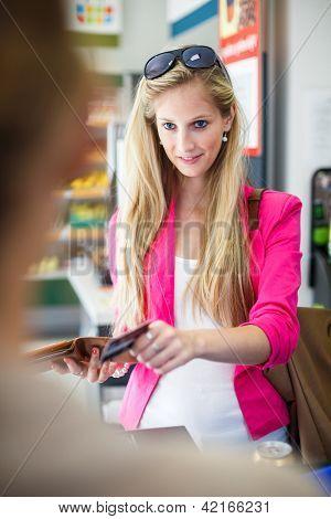 Bela jovem pagar por suas compras no balcão de um mercearia/supermercado (cor