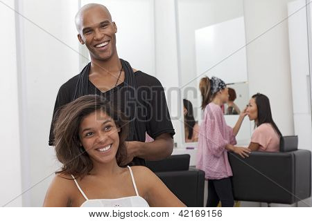Young woman sitting on chair with hairstylist standing behind
