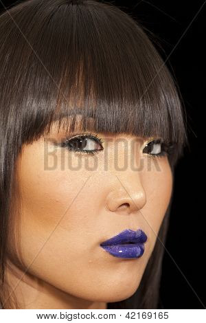 Close-up view of stylish Asian woman wearing blue lipstick