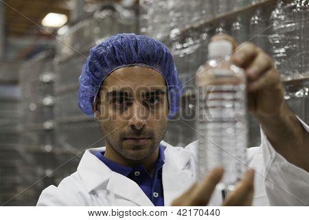 Portrait of factory worker holding water bottle