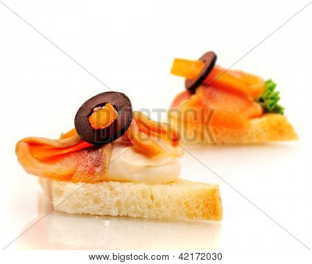 Sandwich on wheat bread with salmon, cream and olive.