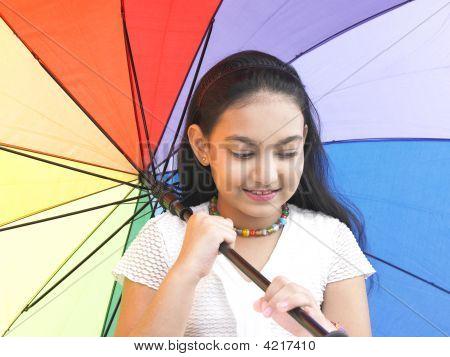 Menina de origem indiana com uma guarda-chuva de arco-íris