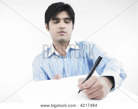 Asian Male Of Indian Origin Writing With A Pen