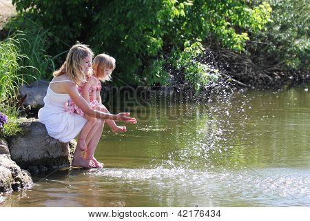 Mãe e sua filha esguichar água no Lago