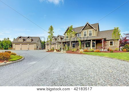 Large Farm Country House With Gravel Driveway And Green Landscape.