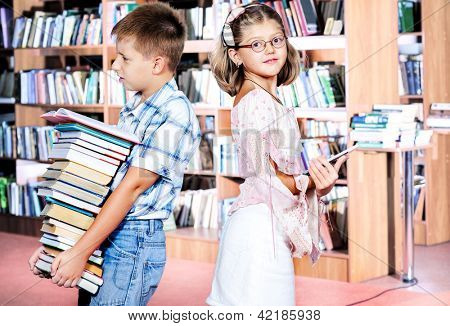 Boy holding pile of paper books and girl with an electronic book