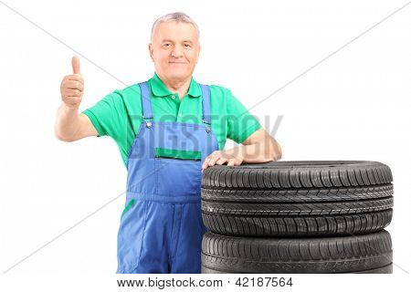 A mature worker posing on car tires and giving thumb up isolated on white background
