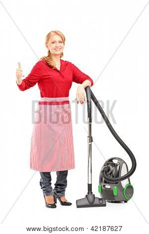 Full length portrait of a blond housewife posing on a vacuum cleaner and giving thumb up isolated on white background