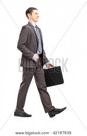 Retrato de cuerpo entero de un joven empresario con maletín caminar aislado sobre fondo blanco