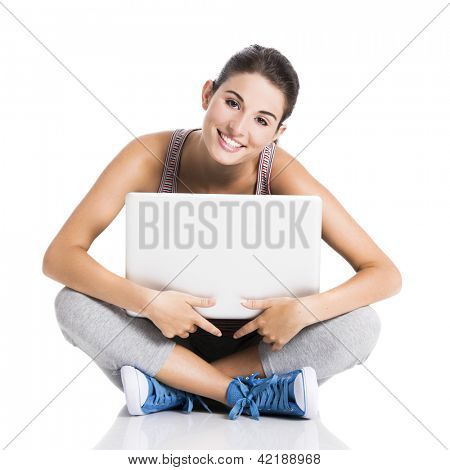 Beautiful student smiling and sitting in the floor with a laptop, isolated over a white background