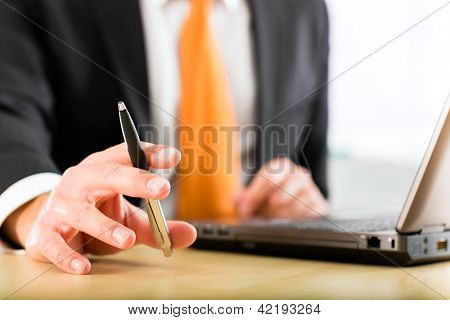 Business - Boss in his office checking mails, in his hand he holds a pen, closeup