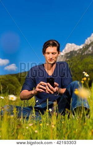 Young man with mobile phone sitting in the meadow with mountain view playing with mobile phone or smartphone
