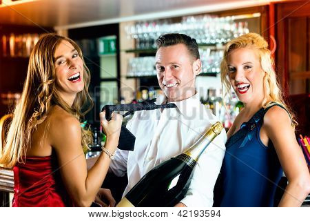 Good friends - bartender and women - with a large magnum bottle champagne at bar having fun, she pulls on his tie