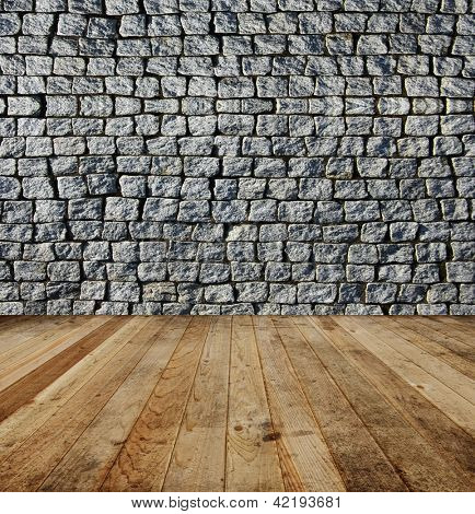 Old grey square brick wall and wooden floor.