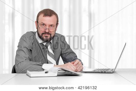 Senior Business Man Sitting By His Desk In The Office