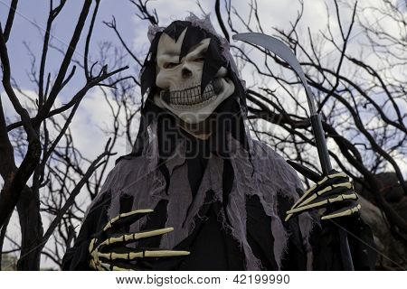Low angle view of boy dressed up as grim reaper holding spade