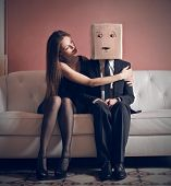 beautiful woman embraces elegant man with box on his head sitting on the couch