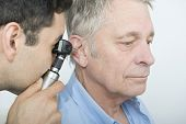 picture of otoscope  - Male doctor checking patient - JPG