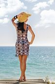 stock photo of braless  - View of a beautiful woman in transparent dress in the beach bathed by the sunny rays of Summer - JPG
