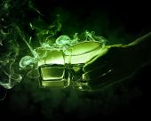 pic of absinthe  - Hand holding one of two glasses of green absinth with fume going out - JPG