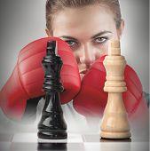 Постер, плакат: Женский боксер с кулаками поднял за шахматной доске