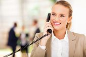 stock photo of half-dressed  - happy female office worker talking on landline phone - JPG