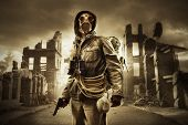 stock photo of post-apocalypse  - Post apocalyptic survivor in gas mask destroyed city in the background - JPG