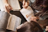 stock photo of conversation  - A group of young women bow their heads and pray with bibles - JPG