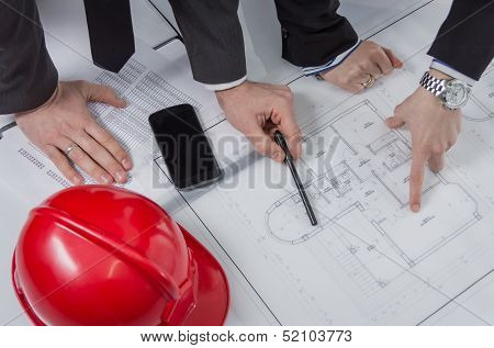 Above View Of Architects Hands Revising A House Project