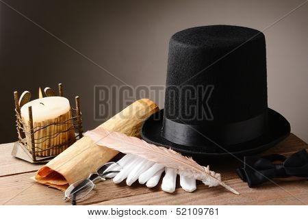 Still life with and old hat gloves quill candle and parchment on rustic wooden table. Horizontal format with warm colors and a light to dark background.