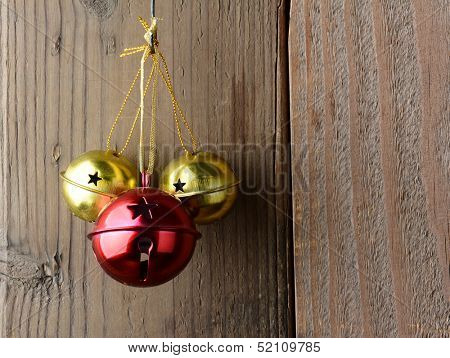 Red and Gold Jingle Bells hanging on a rustic wooden wall.