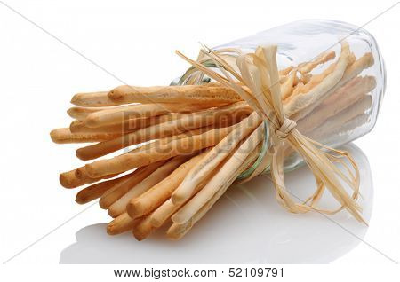 A jar of breadsticks laying on its side on a white reflective surface. The neck of the glass is tied with raffia. Horizontal format.