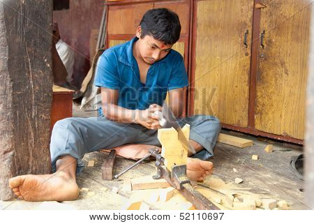 BHAKTAPUR, NEPAL-MAY 20: Unidentified carpenter sawing a board  in Bhaktapur, Nepal, on May 20. 2013. Much of Nepal's economy still relies on hand tools and skilled tradesmen.