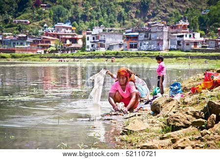 POKHARA,NEPAL-MAY 25:Family washing cloth in Fewa lake on May 25, 2013, Pokhara,Nepal.One of the most beautiful Lakes of Pokhara Valley is the well-known Phewa Lake.