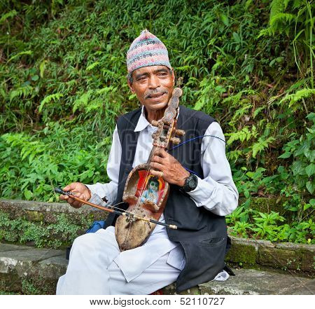 POKHARA - MAY 22: Unidentified Nepalese playing a kind of fiddle, traditional musical  instrument, on May 22, 2013 in Pokhara, Nepal. Poor Nepalese people playing to earn some money from tourists.