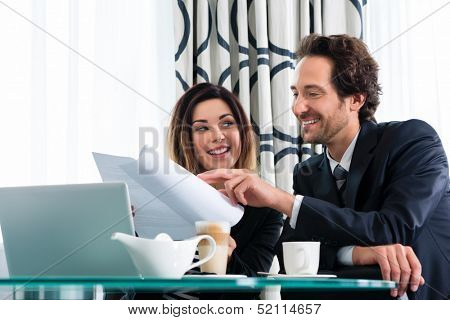 Businesspeople in a business hotel discussing some documents, maybe they are working on a contract
