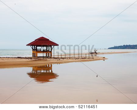 Sandy beach on Koh Samui. The red beach wooden arbor is picturesquely reflected in water